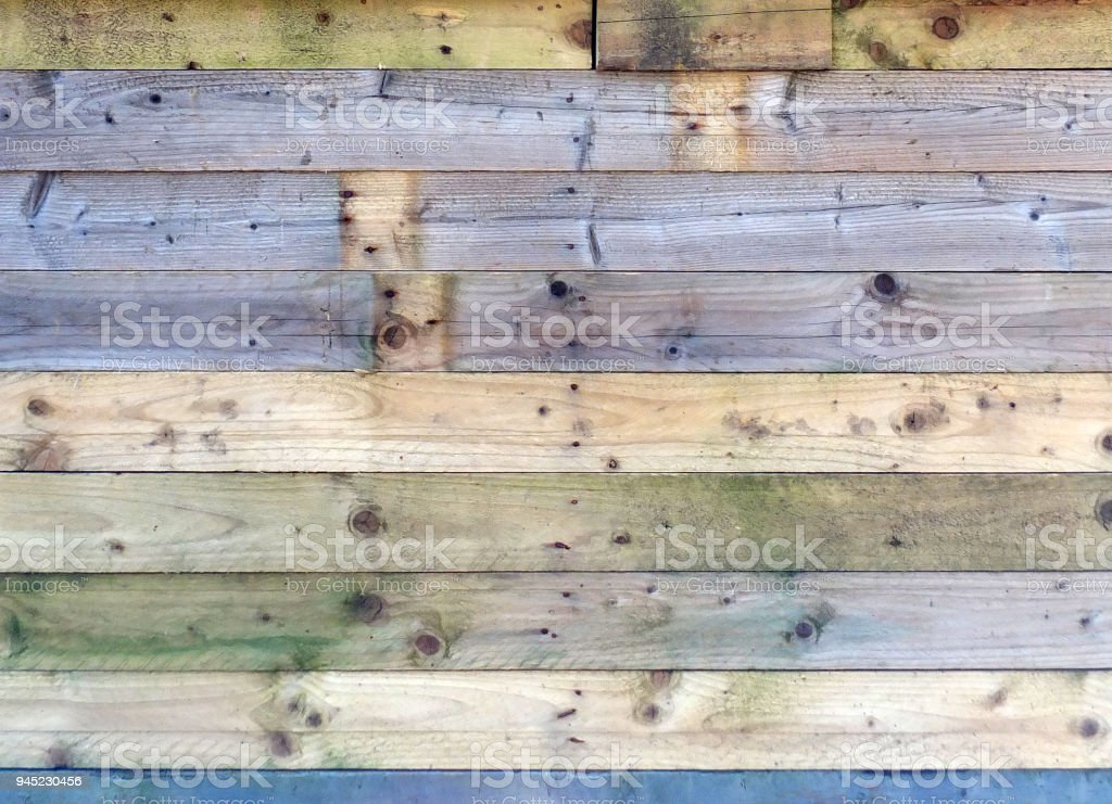 colorful old rustic wooden plank wall or floor with some of the boards stained blue made of patched reused timber stock photo