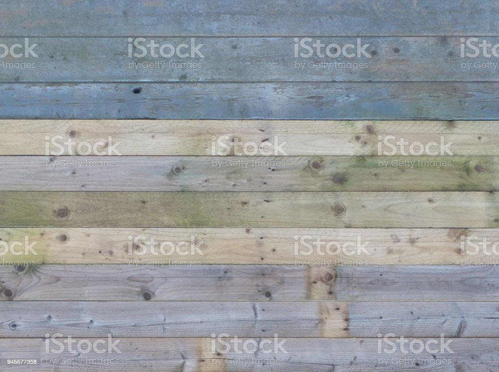 colorful old rustic wooden plank wall or floor with some of the boards stained blue made of reused timber stock photo