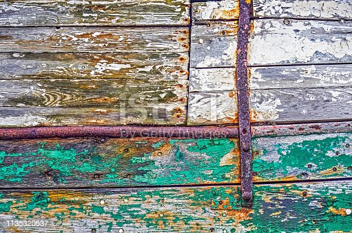 Fragment of a ship hull made of wooden planks and pieces of metal, with peeling green and white paint and sports of rust