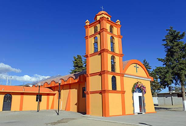 Colorful Orange Church with blue sky background, Mexico Colorful Orange Church with blue sky background located near borders of Veracruz and Puebla, close to Pico de Orizaba, Iztaccihuatland Popocatepetl volcanoes, Mexico orizaba stock pictures, royalty-free photos & images