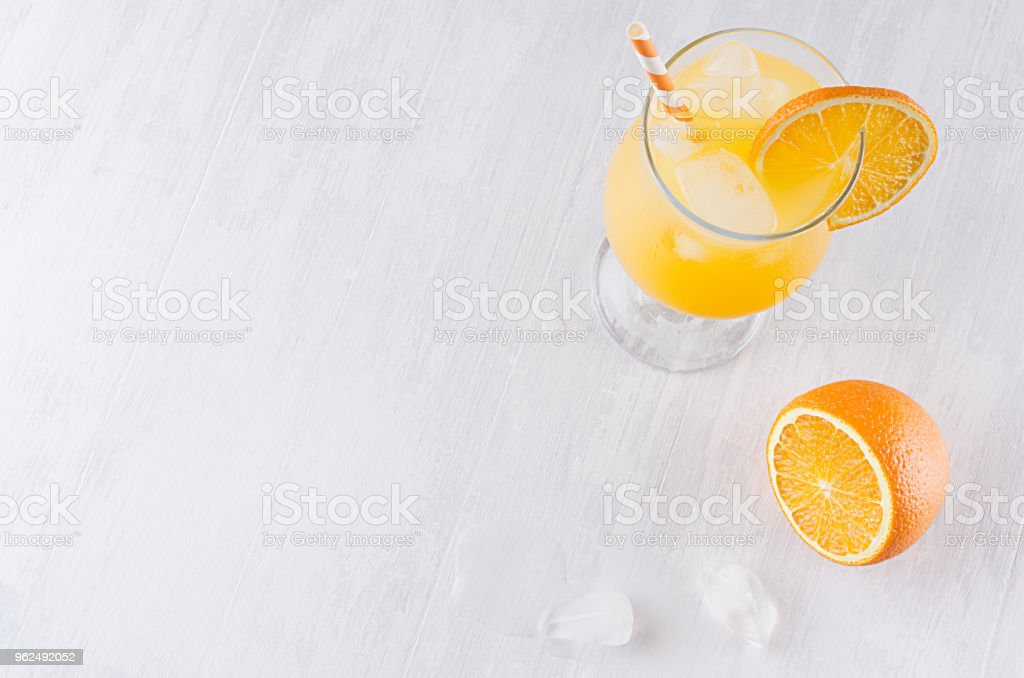 Colorful orange cool citrus cocktail with slice oranges, ice cube, straw on white modern wooden background, top view. - Royalty-free Alcohol Stock Photo