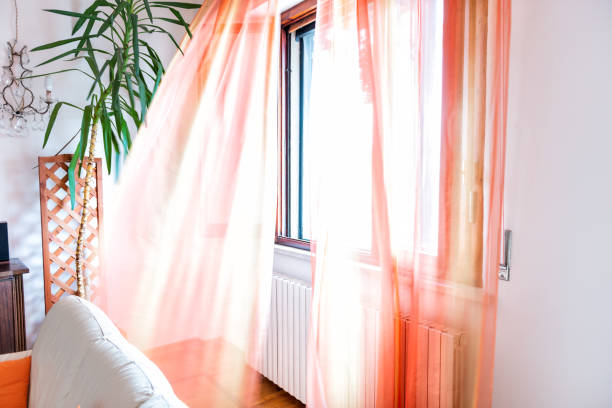 Colorful orange open window curtains blinds in room interior indoors apartment flowing in wind in Italy stock photo