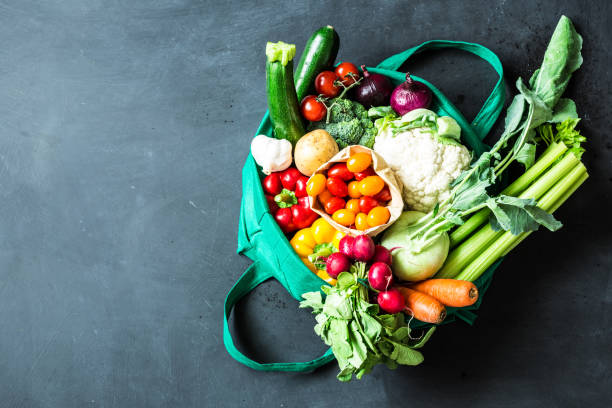 colorful organic vegetables in green eco shopping bag - food delivery imagens e fotografias de stock