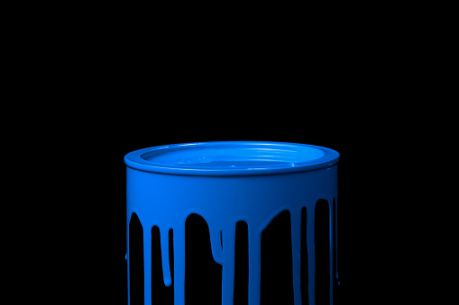 Colorful paint leaking down over the part of metal bucket. Isolated over black background