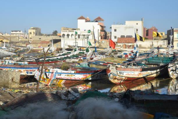 colorful painted pirogues moored in the fisherman's wharf of saint louis, senegal - st louis стоковые фото и изображения