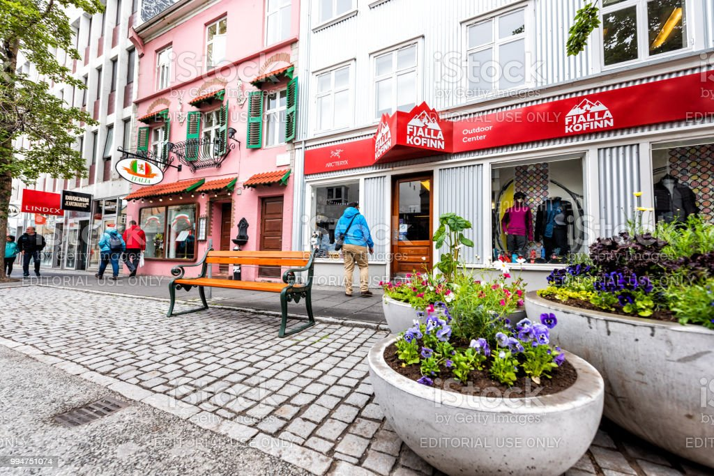 Colorful painted red, pink buildings architecture, with signs for Fjalla Kofinn outdoor center, italia, lindex, shop store in downtown capital city Laugavegur street road, bench and potted flower pots decorations stock photo