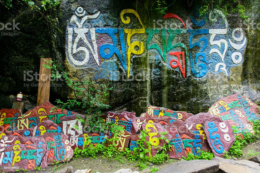 colorful painted tibetan words on rock and wall stock photo