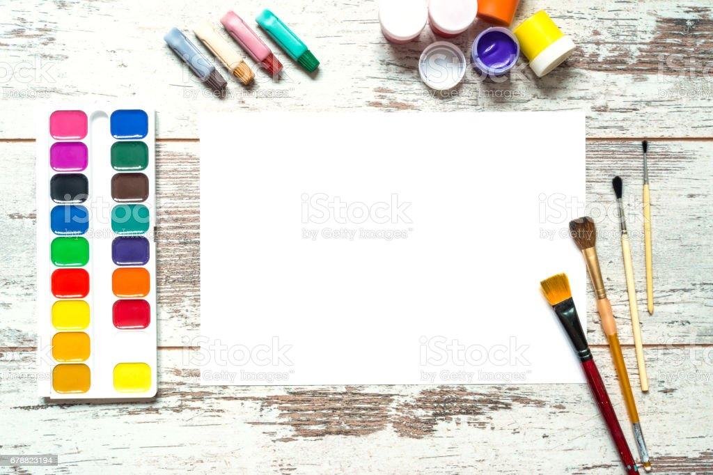 Renkli Boya fırçaları ve bir beyaz izole kağıt yaprağı, guaş, eski bir vintage ahşap arka plan üzerine suluboya, çatlaklar ahşap aşınmış panoları ile. Üstten Görünüm. royalty-free stock photo
