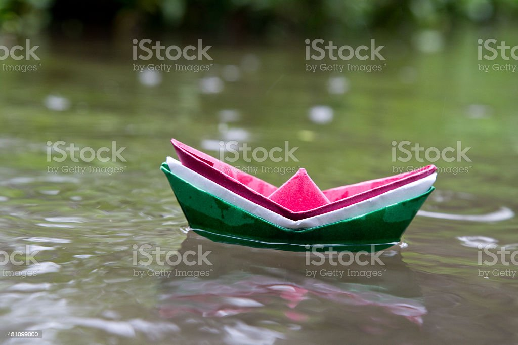 Colorful paper boat floating on water stock photo