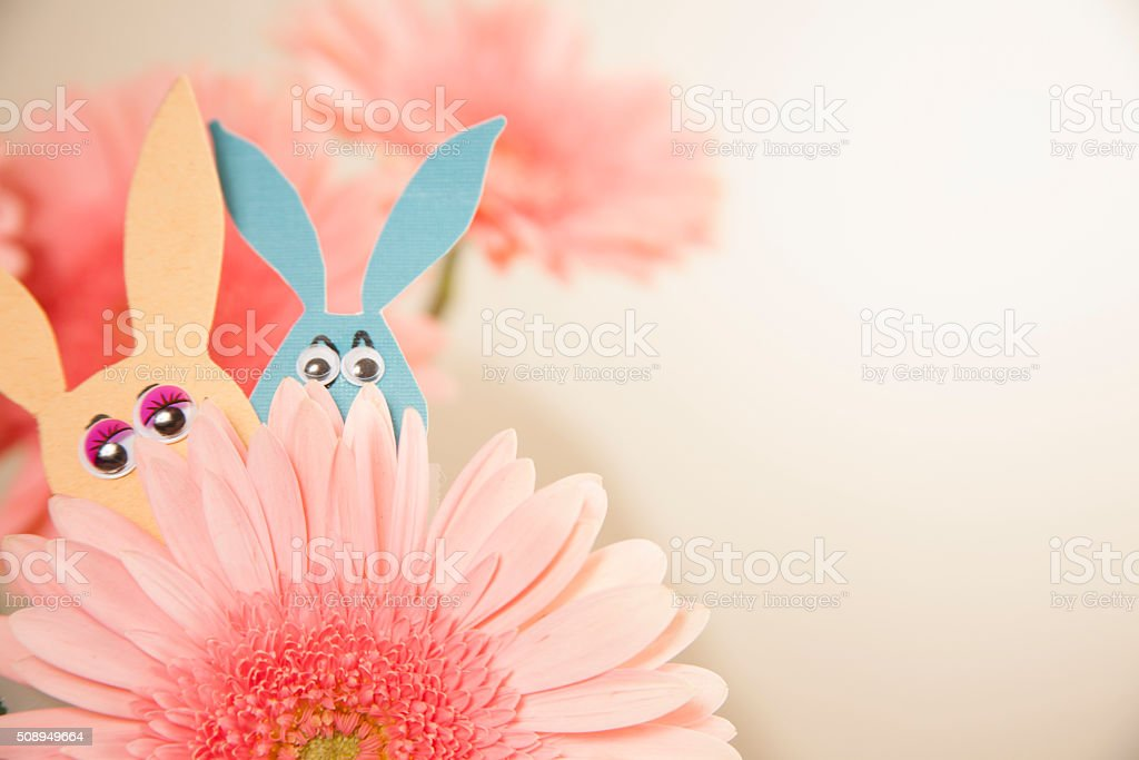Colorful paper Easter bunnies peek out behind flower. stock photo