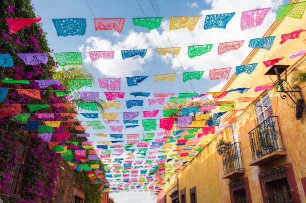banderas de papel de colores sobre la calle en un día soleado - bandera mexico fotografías e imágenes de stock
