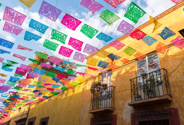 colorful paper flags over street - mexico stock photos and pictures