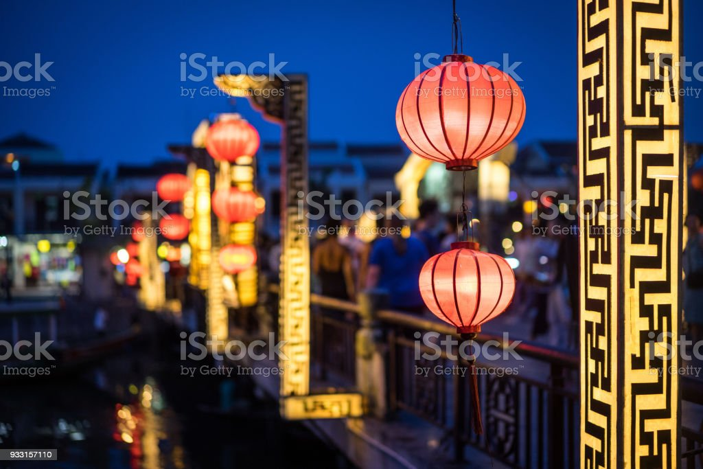 colorful paper lanterns in front of busy street in hoi an vietnam