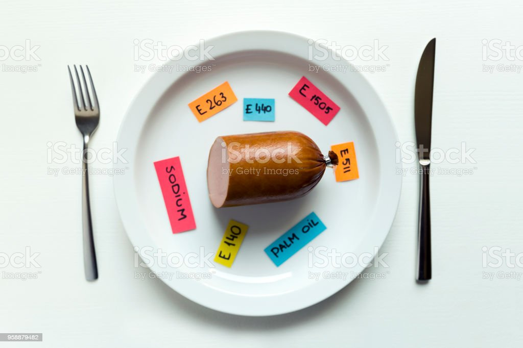 Colorful paper notes naming food additives and sausage on plate with fork and knife, food additive and unhealthy food concept. stock photo