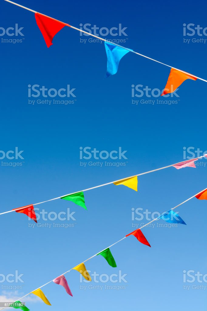 Colorful party flags against blue sky. stock photo