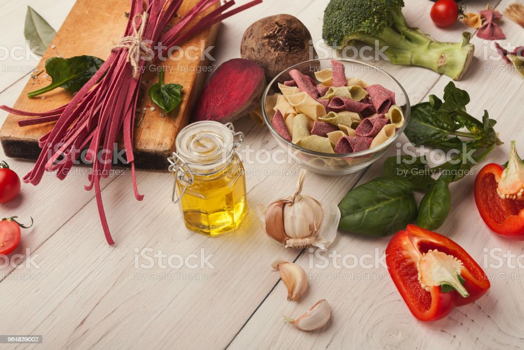 Colorful pasta and cooking ingredients on white wood royalty-free stock photo