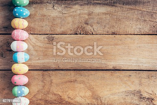 istock Colorful pastel easter eggs on wooden background with space. Vin 627919860