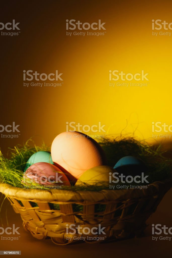 Colorful pastel monophonic traditional painted Easter eggs in basket with green grass on dark yellow background with black shadows, silhouette, light. Copy space for advertisement. With place for text stock photo