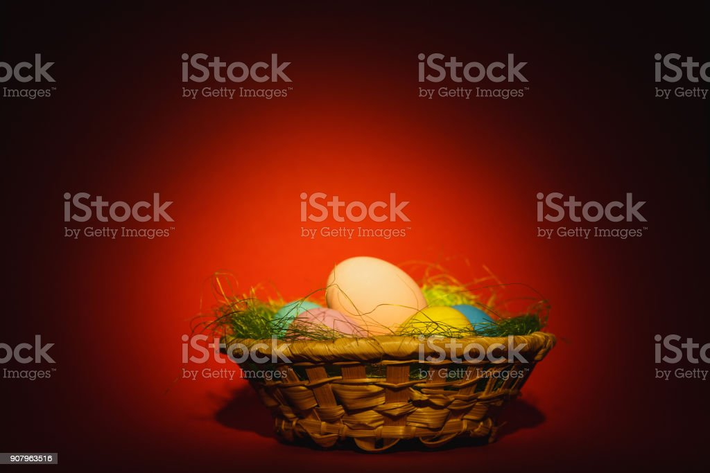 Colorful pastel monophonic traditional painted Easter eggs in basket with green grass on dark red background with black shadows, silhouette, light. Copy space for advertisement. With place for text stock photo