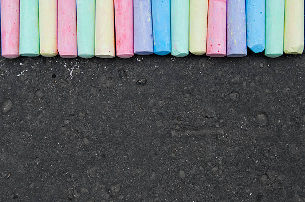 colorful pastel sidewalk chalk on dark asphalt background. - chalk drawing stock photos and pictures