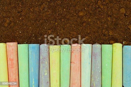 istock Colorful pastel sidewalk chalk on dark asphalt background. 538346234