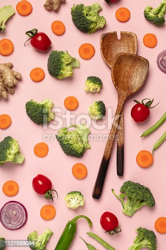 Colorful pattern of tomatoes, broccoli, carrots, ginger and onion with wooden salad spoons on a pink background. Top view of sliced seasonal vegetables. The concept of a healthy diet