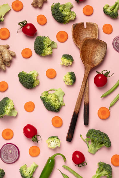 Colorful pattern of tomatoes, broccoli, carrots, ginger and onion on a pink background stock photo