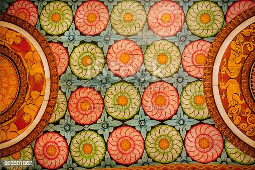 istock Colorful patterns of the old paintings, flowers and decor on wooden ceiling of Buddha ancient temple. 923301062