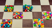 Colorful pebbles spread on checked board background