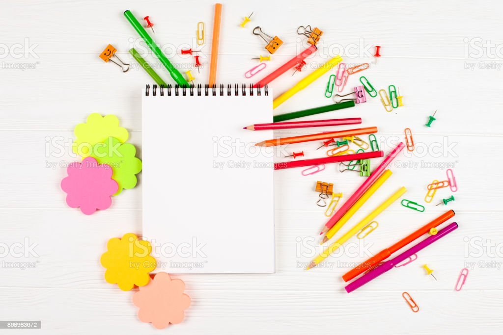 Colorful pencils and felt-tip pens, color notepaper, paper clips, stationery nails on white wooden background stock photo