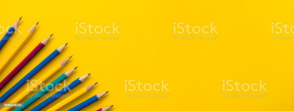 Colorful pencils at border of banner yellow background stock photo