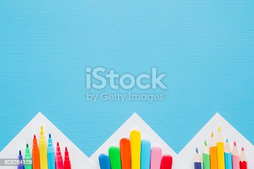 istock Colorful pencils, crayons and color pens on white papers corners. Empty place for text or drawing on the blue background. Childhood creative art concept. 925264128
