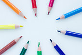Colorful pencils pointing to the middle forming a circle on white background