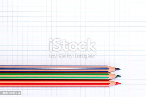 istock Colorful pencils of red, green and blue colors on a checkered exercise book paper with copy space 1050736384