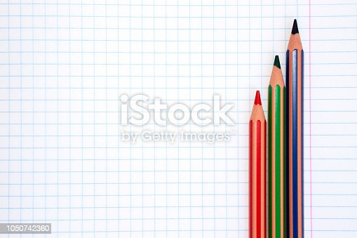istock Colorful pencils of red, green and blue colors on a checkered exercise book paper with copy space 1050742360