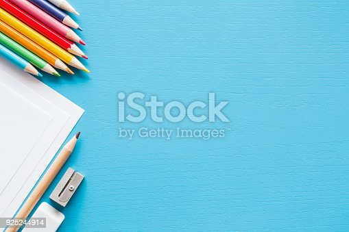925244914 istock photo Colorful pencils, white papers and metal pencil sharpener. Empty place for text or drawing on the blue background. Childhood creative art concept. Flat lay. 925244914