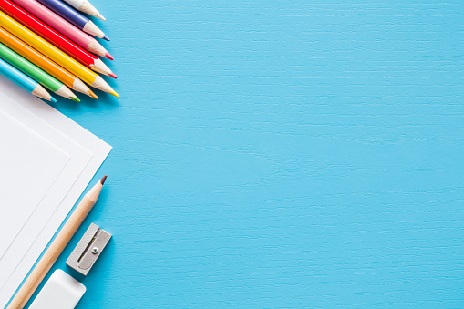 Colorful pencils, white papers and metal pencil sharpener. Empty place for text or drawing on the blue background. Childhood creative art concept. Flat lay.