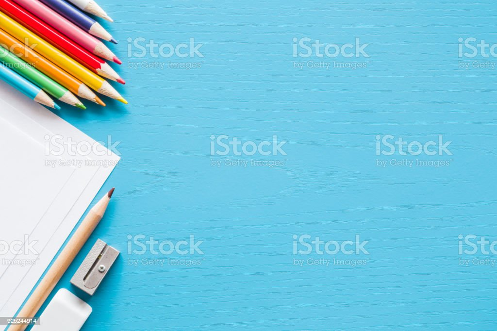 Colorful pencils, white papers and metal pencil sharpener. Empty place for text or drawing on the blue background. Childhood creative art concept. Flat lay. stock photo