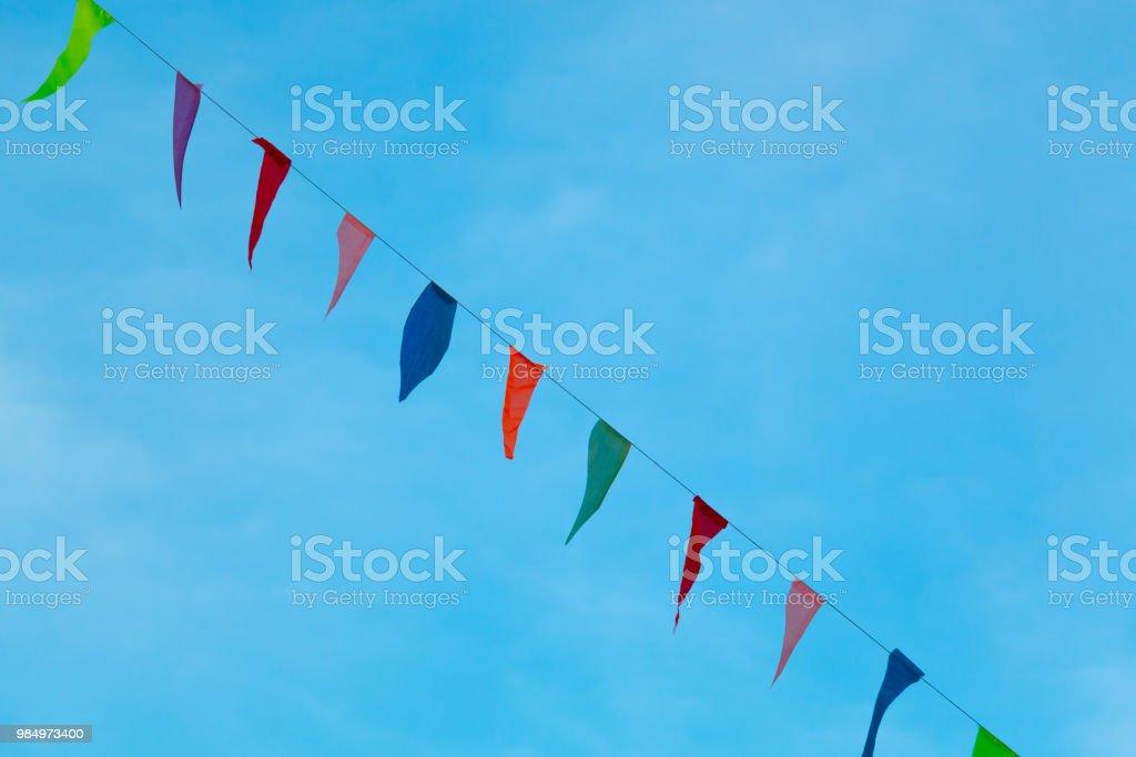 Bunte Wimpel hängen mit einem Seil gegen blauen Himmel. – Foto