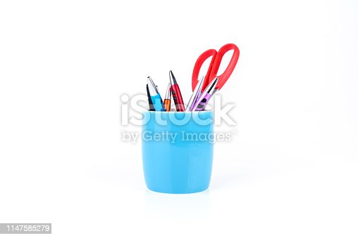 Colorful pens and orange scissors are in blue mug isolated on white background.