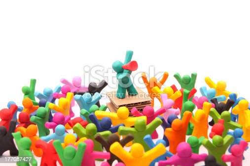 determined plasticine guy standing on a pedestal talking to a colorful croed through a red bullhorn - isolated on white