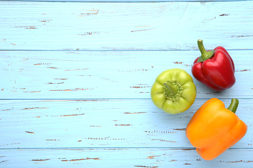 Green , yellow and red bell pepper on wooden background