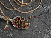 Colorful peppercorn in old vintage spoon and jute rope on gray textured concrete background with copy space. Top view or flat lay. Food background