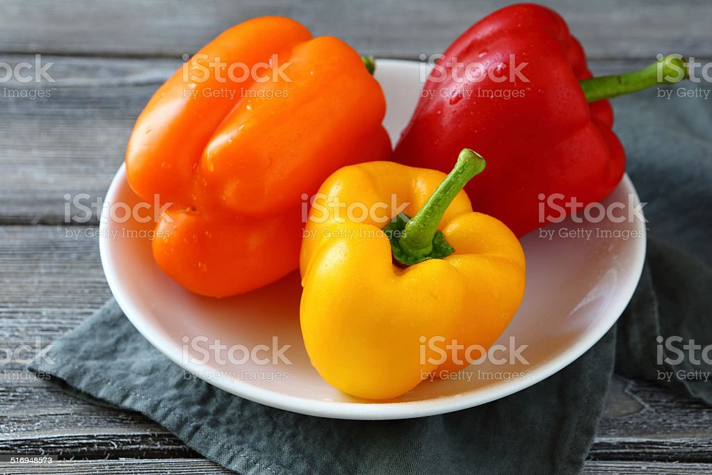 colorful peppers on a white plate stock photo