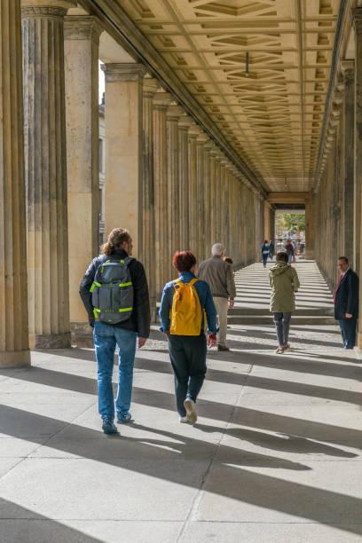 Bunte Perspektive von Menschen, die unter einem antiken griechischen Bau wandeln, der gemusterte Schatten auf der Museumsinsel im Stadtteil Mitte zeigt – Foto