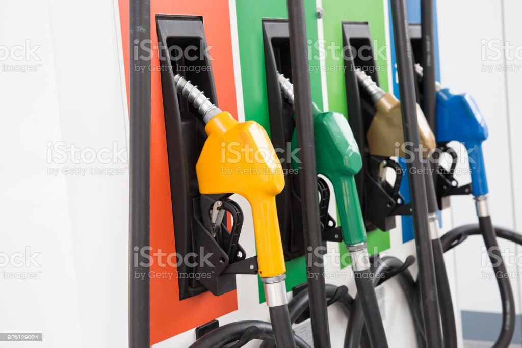 Colorful Petrol pump filling nozzles isolated on white background stock photo