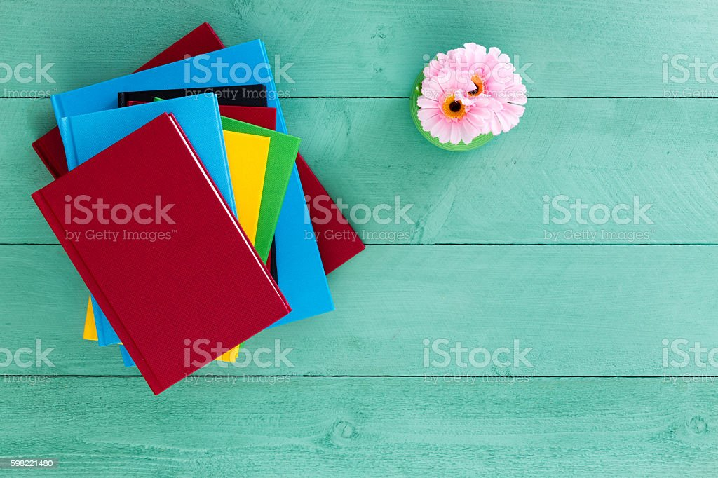 Colorful pile of books stacked on a green table stock photo