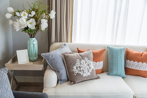 Colorful pillows on beige sofa with flowers in living room.