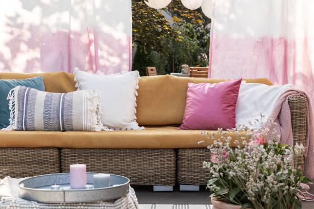 Bunte Kissen auf Rattan-Sofa auf der Terrasse mit Blumen, bemalten Vorhängen und Kerzen. Echtes Foto – Foto