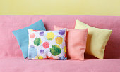 Colorful pillows on pink sofa